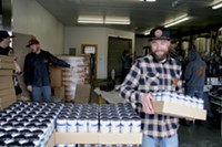 Riverbend's head brewer, Chasen Schultz loading a case of Blunder Armour at the brewery.