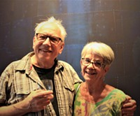"""Bill Hoppe and Sandy Anderson standing in front of """"West Went,"""" created by Hoppe in 2015."""