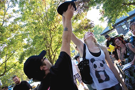 AND . . . ACTION! Susie Heyden pulls her team's film genre from a hat last Friday in Railroad Square.