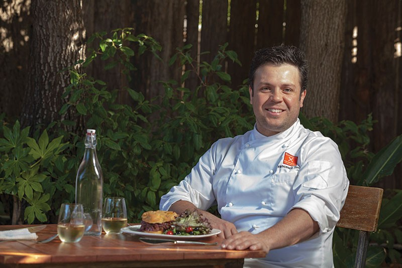 AT THE HELM Francesco Torre on the Canneti patio with his rosemary focaccia and pork sausage sandwich. - MICHAEL AMSLER