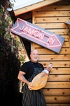 <b>COME ON IN</b> Mark Stark hams it up outside his fifth Sonoma County restaurant.