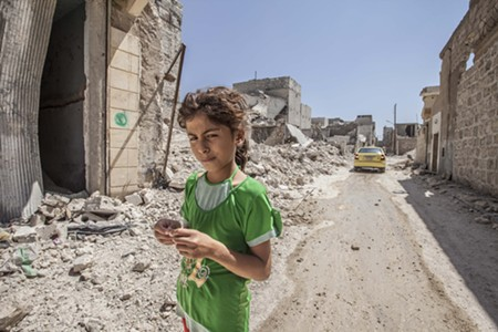 FACE OF WAR A girl walks through the rubble of a battered neighborhood in Aleppo, Syria.