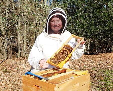 FLOATS LIKE A BUTTERFLY  April Lance shows off a healthy honeycomb - WILL BUCQUOY