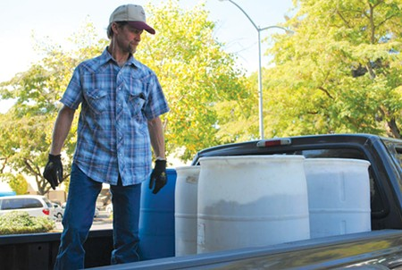 GRAINS TO GO Windor's Rick Olufs loads 350-pound barrels of barley onto his truck. He'll feed it to his cattle.