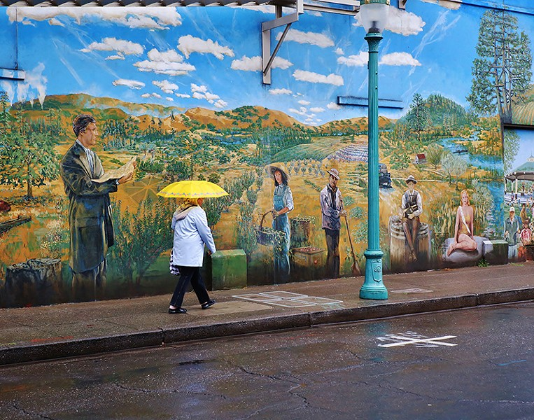 HALCYON DAYS A woman walks past a mural in downtown Healdsburg depicting the region's agricultural history. Despite the deluge, it would take substantial downpours to reach even the dismal water levels of the 1977 drought. - WILL BUCQUOY