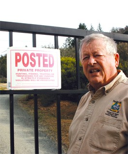 HIDDEN ACTIVITY: Jim Doerksen at the gate to Cornell's proposed winery, where unpermitted tree and brush removal has caused harmful erosion to a creek once teeming with salmon. - GABE MELINE