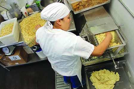 IT'S A-MAIZING!  Corn goes in, masa comes out as Adriana Guzmán grinds nixtal for El Molino Central's daily dough.