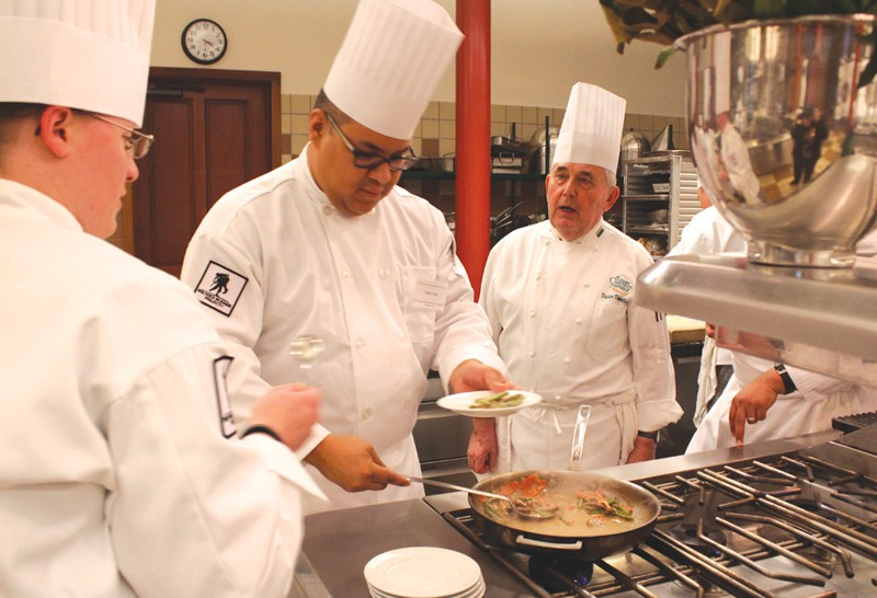 LIFE AFTER WARTIME Dieter Doppelfeld, right, helps students plate food they've cooked at culinary boot camp.