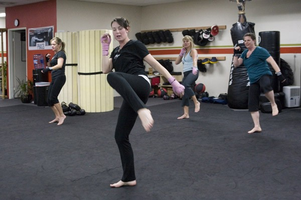 LIGHT ON THEIR FEET Christie Checketts leads a women's kickboxing class in Santa Rosa. Originally a Thai discipline and once a competitive sport, kickboxing has expanded into fitness and self-defense. (L-R: Jayme Beals, Checketts, Cindy Erickson, Sally Genilio) - MICHAEL AMSLER