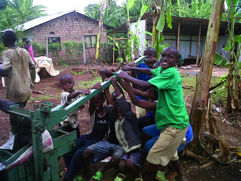 MORTAR Children at the Tuleeni orphanage play with a brickmaking machine bought by Jackie Weiss' group.