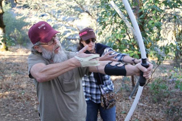 READY, AIM . . . Pat Bohn, archery expert and Dry Creek Gun Club member, shows a fellow member how to use a homemade hunting bow. - JENNIFER DURBAN