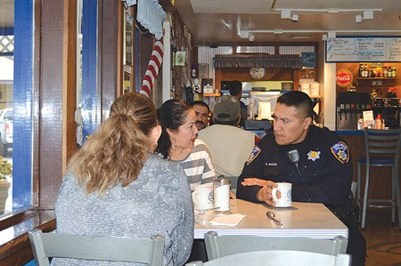 BLACK AND BLUE A Santa Rosa police officer meets with residents at Sam's For Play Cafe.