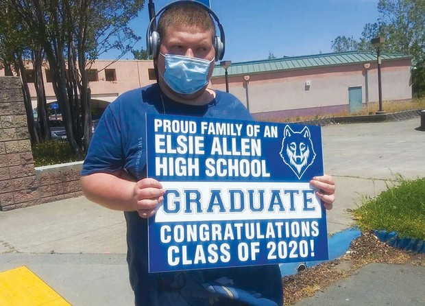 CLASS OF 2020 Elyon Cannabis printed graduation signs like the one held by this unidentified high school graduate. - JONAH RASKIN