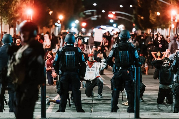 """Marqus """"Red Bear"""" Martinez kneels in front of the police officers and asks them to be in solidarity with the protesters."""
