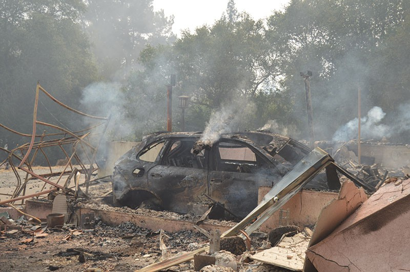 A car smolders in the Rincon Valley on Monday morning - TOM GOGOLA
