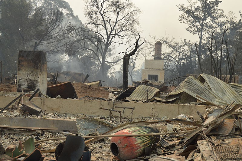 Chimneys and refrigerators were all that were left standing at many homes burned in Monday's blaze. - TOM GOGOLA