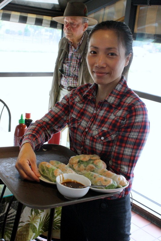 A waitress serves salad spring roles at Ben Thanh