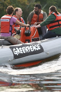 GREENPEACE - AN ACTIVE RIDE: Kumi Naidoo (second from right) tours Mountain Island reservoir with locals.