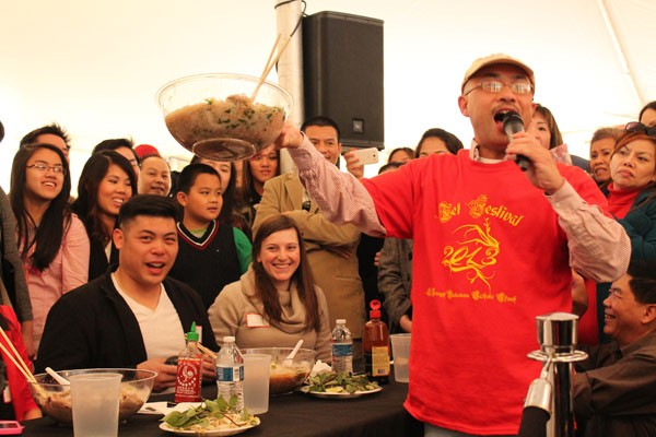 An announcer for the Pho eating competition holds up one of the contestants bowl (Kseniya Martin, pictured sitting at the table on the right) before it is weighed to see just how much she ate.