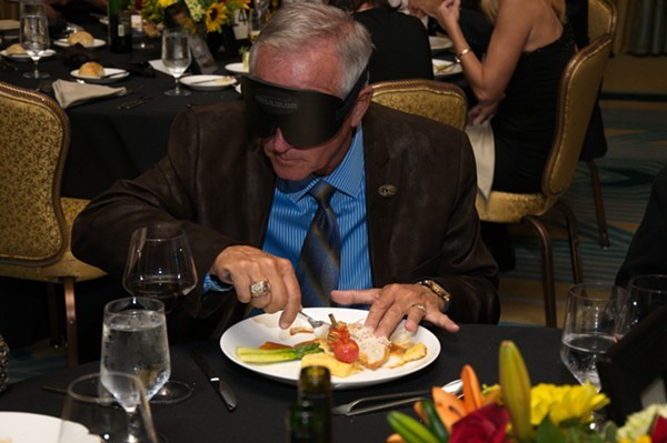 An attendee attempting to eat while blindfolded