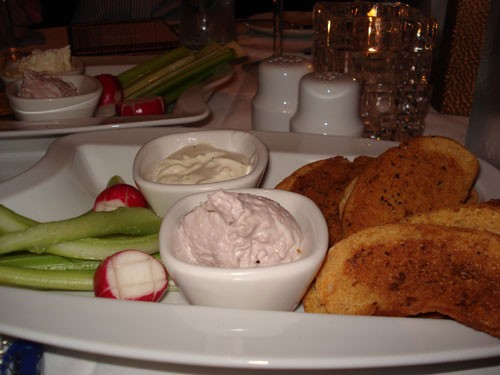 Assorted spreads with crostini and veggies.