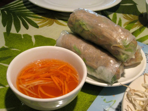 Bi Cuon (Garden Delight Roll) - Shredded pork seasoned with garlic, roasted rice, lettuce, mint, and bean sprouts rolled in rice paper, served with sweet and sour garlic sauce.