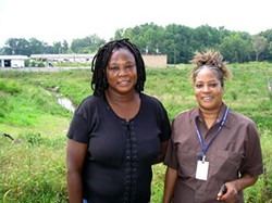 SAM BOYKIN - Carolyn Johnson and Sheila Marrow stand in front of the Hidden Valley Ecological Garden project in their north Charlotte neighborhood.