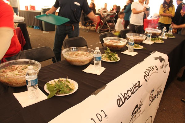 Contest officials set up the table for the pho eating contest