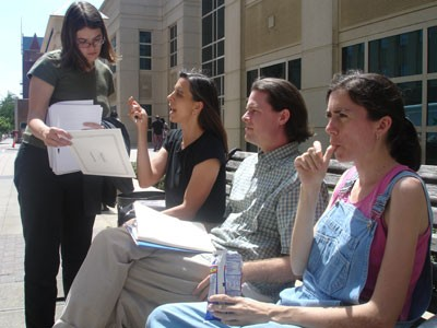 Durham resident Beth Brockman (second from left) discussed legal strategy with Duke Divinity School student Sheila McCarthy while Scott Langley and Sheila Stumph waited for their hearing at the Wake County District Court on April 20; Stumph and seven others would be arrested again that same night. - JESSE DECONTO