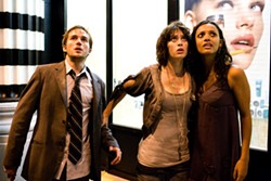 SAM EMERSON / PARAMOUNT - FRIGHT-SEEING IN NEW YORK: Even the background ad seems to be reacting to the creature attacking Manhattan in Cloverfield, starring (from left) Michael Stahl-David, Lizzy Caplan and Jessica Lucas.
