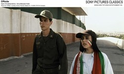 SONY PICTURES CLASSICS & CTB FILM CO. - GAME DAY A soldier (Karim Khodabandehloo) escorts a young woman (Sima Mobarak Shahi) to the stadium's makeshift holding pen in Offside