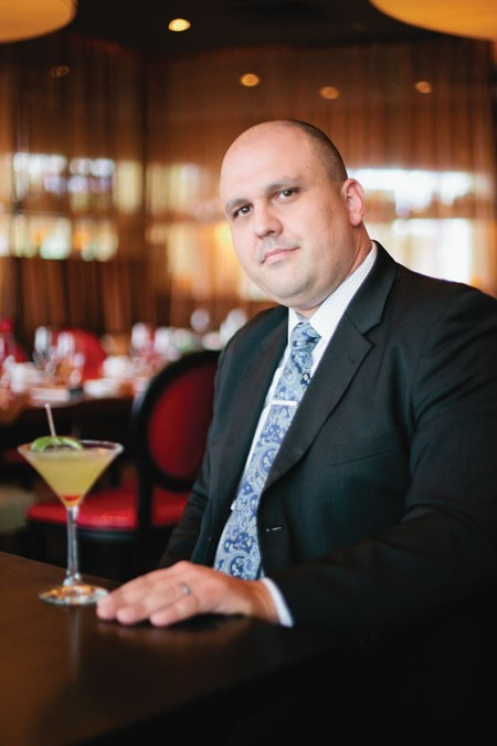 General Manager Aaron Ward with a signature cocktail - LOGAN CYRUS