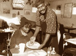 RADOK - GRANDMA'S COUNTRY KITCHEN Abdul Bilal serves up traditional Southern fare to a customer at North Tryon Eatery