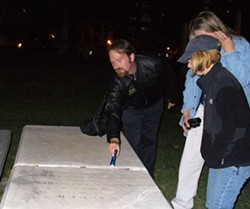 Jason and Julie from N.C. Paranormal investigate a grave at Settlers Cemetery, alongside  CL staffer Heather Desmond (sporting a cap). - JARED NEUMARK