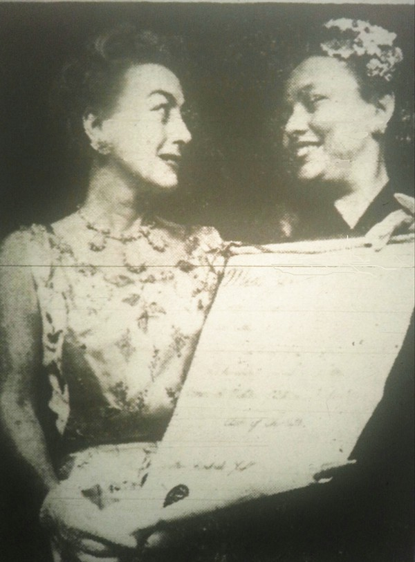 Joan Crawford, left,receiving an award from a member of Charlotte society in the late 1950s.