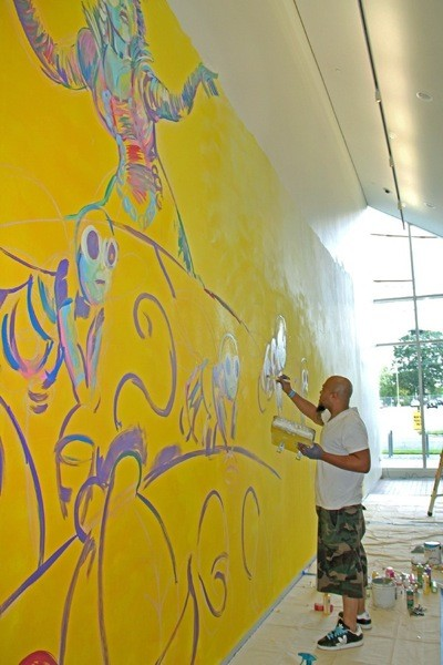 John Hairston working on the mural Rhymes for Reason