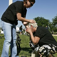 """Laurie Sirko (L) comforts her mother Summer Lipford, next to a pair of military boots bearing the name of her son, U.S. Army Pfc. Steven Sirko, during the """"Eyes Wide Open: The Human cost of War"""" exhibition on the National Mall, May 12, 2006, in Washington, D.C."""