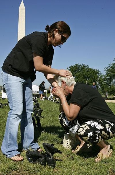 """Laurie Sirko (L) comforts her mother Summer Lipford, next to a pair of military boots bearing the name of her son, U.S. Army Pfc. Steven Sirko, during the """"Eyes Wide Open: The Human cost of War"""" exhibition on the National Mall, May 12, 2006, in Washington, D.C. - CHIP SOMODEVILLA"""