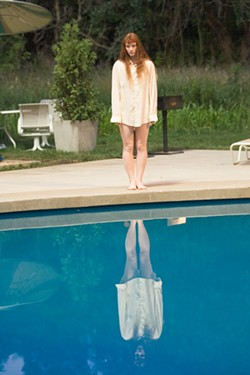 FRANK MASI / WARNER - LIQUID LOUNGE Sea nymph Story (Bryce Dallas Howard) lingers poolside in Lady In the Water