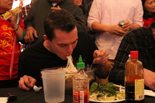 - Matt Poilock shovels noodles into his mouth as he races the clock during the pho eating contest.