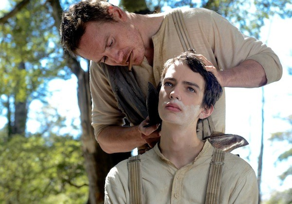 Michael Fassbender (standing) and Kodi Smit-McPhee in Slow West