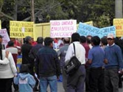 LEW HERMAN - Onlookers gather round a demonstration by Bolivian women in Cochacamba, Bolivia