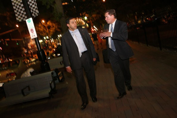 OVERTIME: Bankers Dave Weaver (right) and T.T. Barinath (who's just visiting Charlotte) stroll down Tryon Street - CATALINA KULCZAR