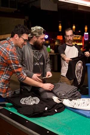 Patrick Tobin, right, shows off merchandise to new members Andrew Arquette, left, and Bobby Demmery, center. - MERT JONES