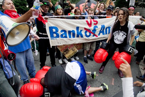 Protesters hold a mock boxing match between Brian Moynihan, president and CEO of Bank Of America, played by Randy Jackson, and the 99 percent, played by LeNina Nabal. (Photo by Grant Baldwin)