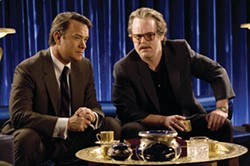 FRANCOIS DUHAMEL / UNIVERSAL - TABLE TALK: Charlie (Tom Hanks) and Gust (Philip Seymour Hoffman) discuss strategy in Charlie Wilson's War.