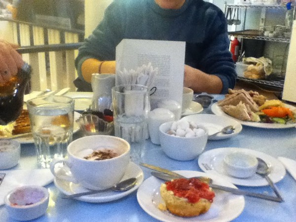 Taken at Willow Tea Rooms in Glasgows city centre, and the dishes in front of me are a cream scone with jam and a cappuccino