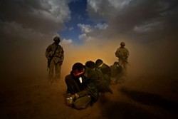 THINKFILM - THE FOG OF WAR: U.S. soldiers stand watch over detainees in Taxi to the Dark Side.