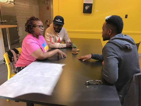 April Hood (from left), Eric Ndelo and Ifeanyi Ibeto plan their grand strategy inside the Hygge coworking space at Camp North End. (Photo by Mark Kemp)