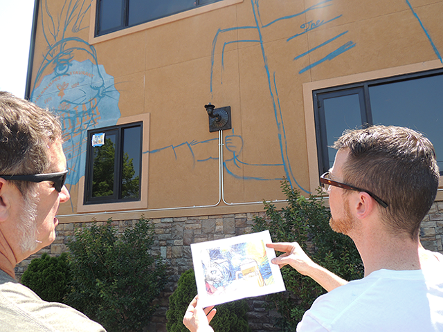 Mike Wirth discusses work on his mural with Peculiar Rabbit owner Rob Nixon. (Photo by Ryan Pitkin)